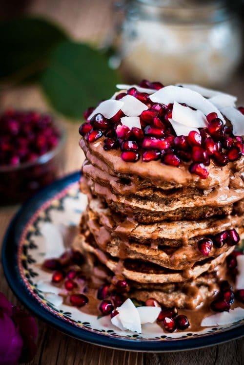Ein Teller mit Pancakes die zu einem Turm gestapelt sind und Granatapfelkernen oben drauf.