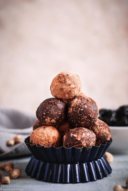 Schokoladen Energy Balls gestapelt auf einer grauen Tischplatte