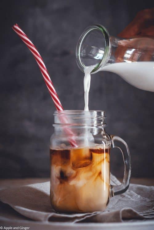 Glas Kaffee mit Strohhalm und Eiswürfeln in das Milch gegossen wird