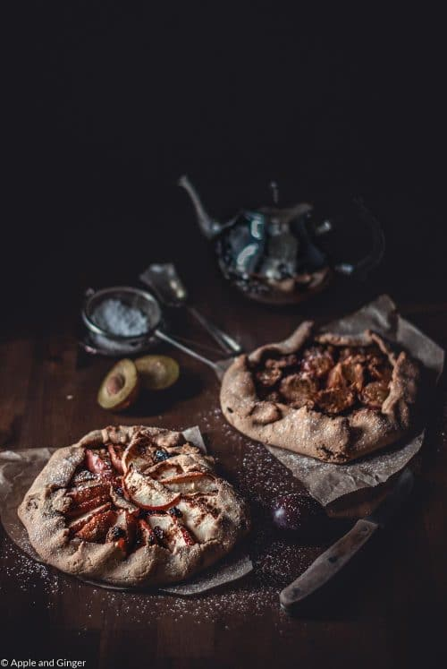 Galettes mit Apfel udn Pflaumen auf einem Holztisch