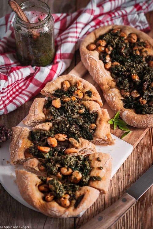 Zwei Pide Brote mit Spinat, Pilzen und Bohnen auf einem Brett