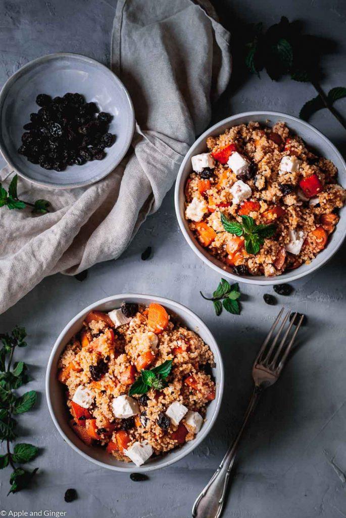 Zwei Schüsseln mit Couscous Salat mit Möhren, Feta und Kürbis auf einem Tisch