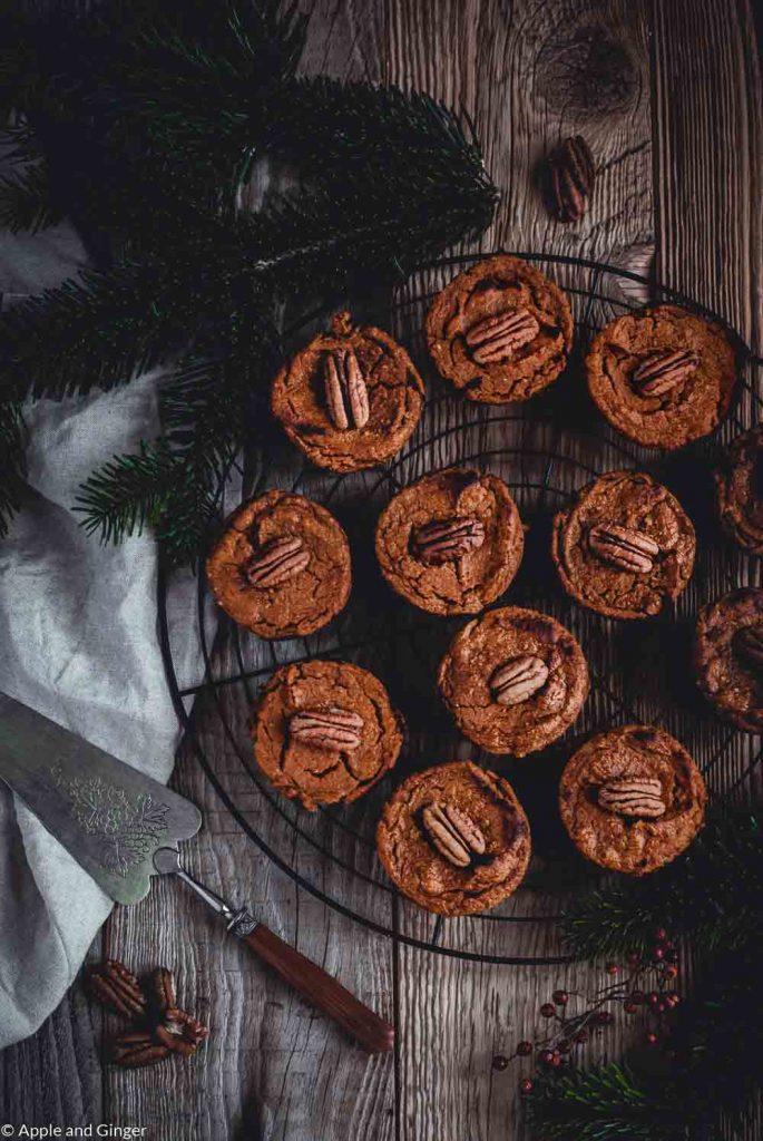 kleine Pumkin Pies auf einem Rost mit Tannenzweigen dekoriert