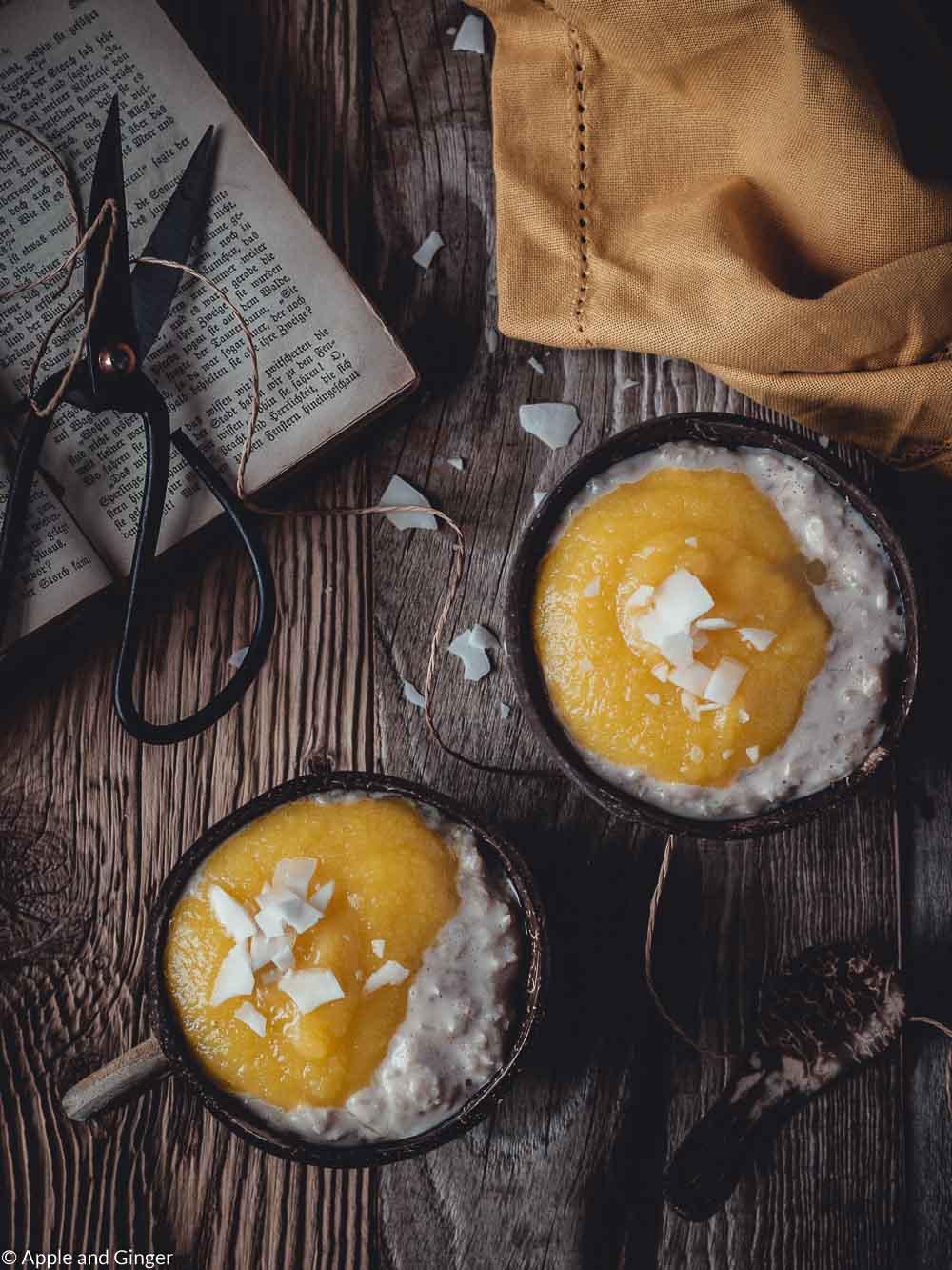 Milchreis mit Mangopüree in zwei Kokosnusschalen