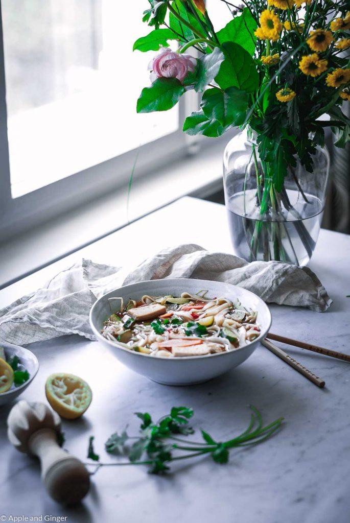 Ein Teller Suppe auf einem Tisch mit Blumen