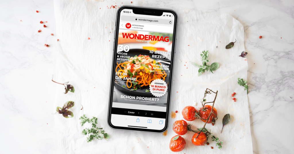 Wondermags Magazin im Handy auf einer Marmorplatte mit Tomaten