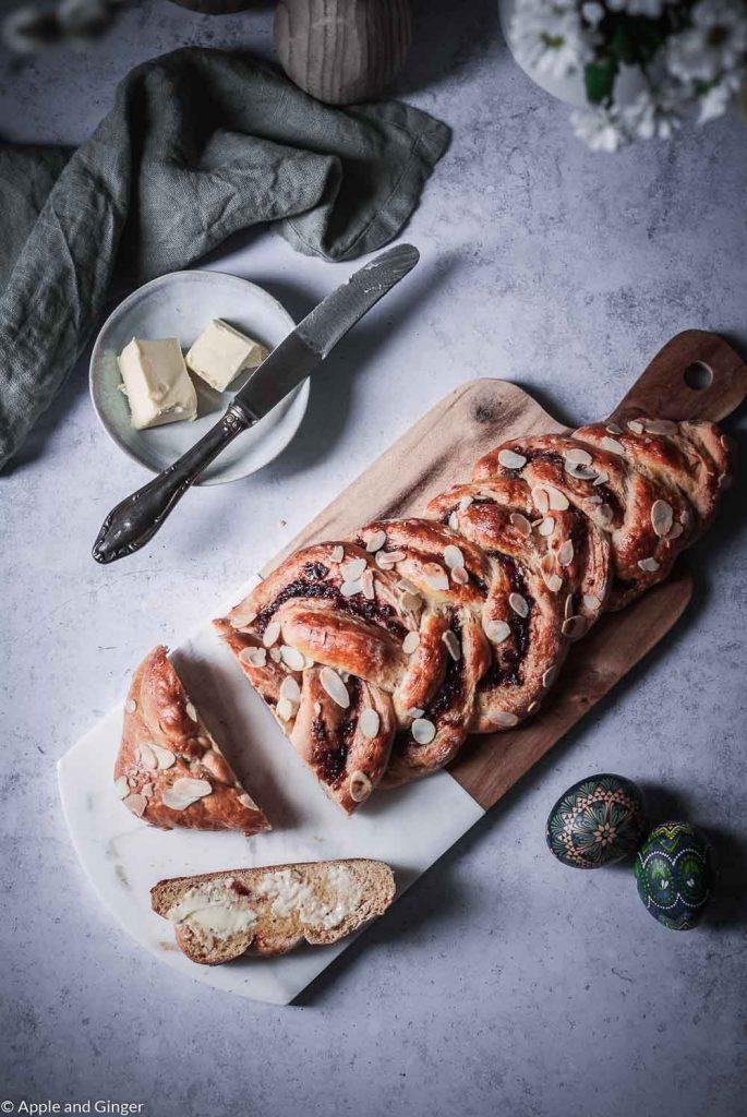 Ein Hefezopf auf einem Tisch mit Osterdeko und Butter