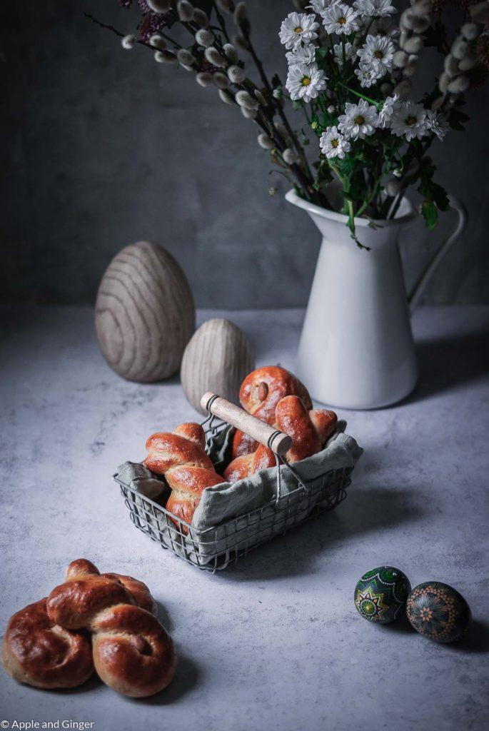 Hefegebäck in einem Korb auf einem Tisch mit Blumen und Osterdeko