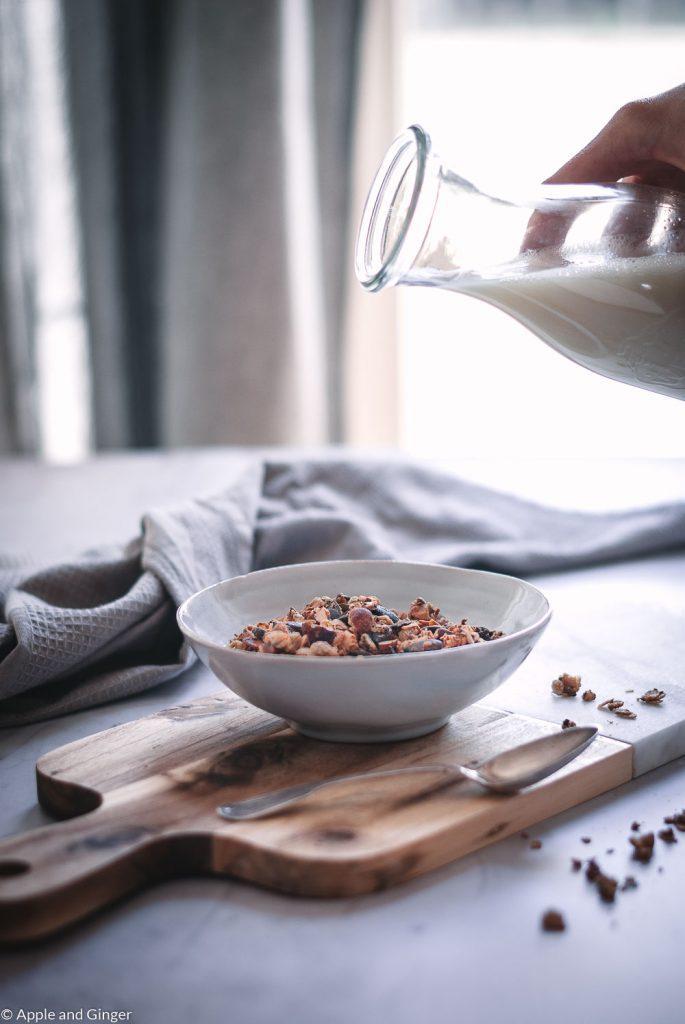 Müsli in einer Schüssel auf einem Tisch mit Milch die eingegossen wird