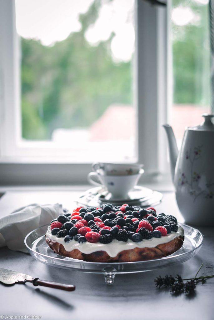 Kuchen mit Beeren auf einer Servierplatte mit Geschirr
