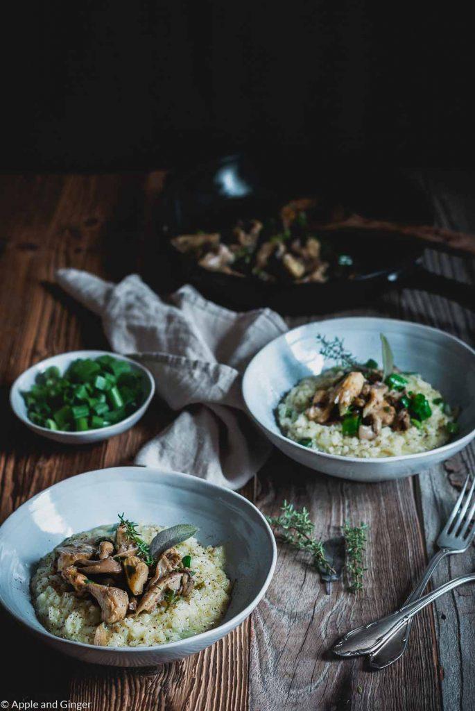 Zwei Teller Risotto mit Pilzen auf einem Holztisch
